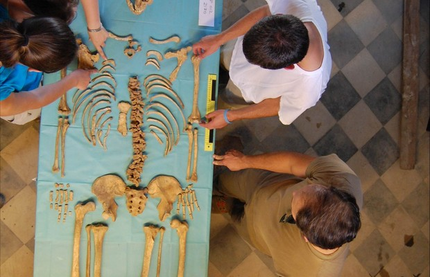 Undergraduate students examine the skeleton of a young male excavated from the Badia Pozzeveri cemetery