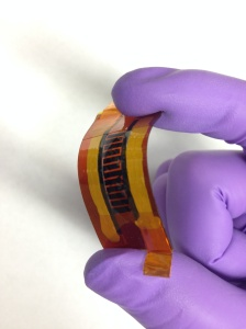 "Rice University scientists made this supercapacitor with interlocked ""fingers"" using a laser and writing the pattern into a boron-infused sheet of polyimide. The device may be suitable for flexible, wearable electronics.  Credit: Tour Group/Rice University"