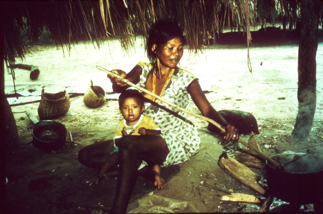 "Photo Credit: Karen Kramer, an associate professor of anthropology, published a study in the Journal of Human Evolution titled, ""When Mothers Need Others: Life History Transitions Associated with the Evolution of Cooperative Breeding."" Her research examines how mothers underwent a remarkable transition from the past – when they had one dependent offspring at a time, ended support of their young at weaning and received no help from others – to the present, when mothers often have multiple kids who help rear other children. In this photo, a Pumé hunter-gatherer woman both cares for her young child and cooks a meal for her older children. Kramer has worked with the Pumé in Venezuela since 2005."