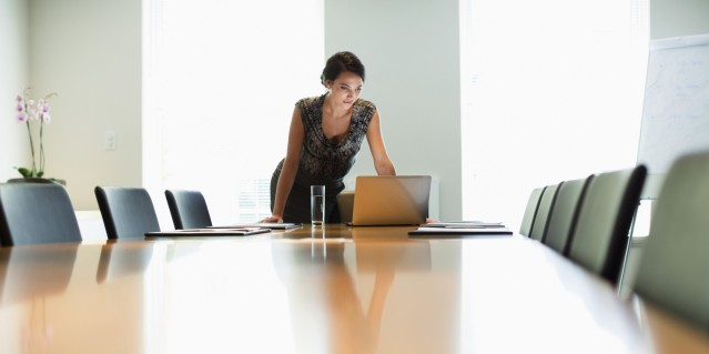 Businesswoman using laptop at conference table