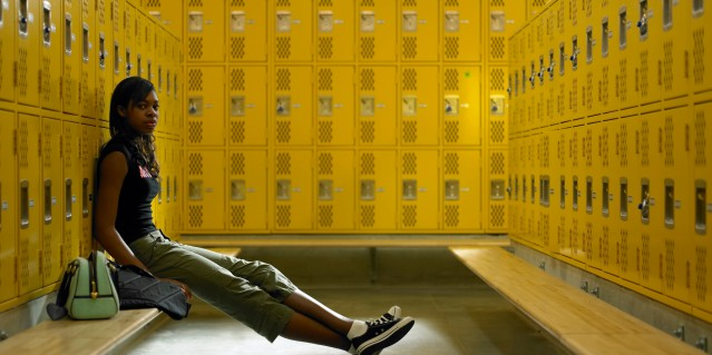 Teenage girl (15-17) sitting in locker room on bench, portrait