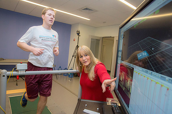 "Irene Davis, a professor of Physical Medicine and Rehabilitation at HMS and head of the National Running Center at Spaulding Rehab in Cambridge (pictured), made a study that shows runners who run ""lightly"" have fewer injuries. On the treadmill is Laboratory Engineer at Spaulding National Running Center, Matthew Ruder. Kris Snibbe/Harvard Staff Photographer"
