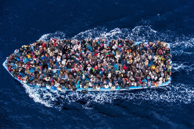 Hundreds of refugees and migrants aboard a fishing boat are pictured moments before being rescued by the Italian Navy as part of their Mare Nostrum operation in June 2014. / The Italian Coastguard / Massimo Sestini