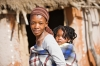 African mother carry child in a traditional way in front of the hut